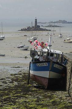 Marée basse en Bretagne et bateau de pêche à quai.