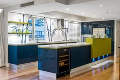 A custom backpainted glass splashback featuring bamboo plants caters to the clients' love of Asia in this apartment kitchen by interior designer Kim Duffin.