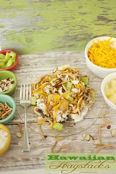 Hawaiian Haystacks recipe has a rice base, white sauce, cheese, pineapples, coconut, chow mein noodles, celery, almonds, cheese, and soy sau...