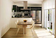 Projetada pela arquiteta Gisele Emery para uma casa em São Paulo, a cozinha se separa da sala de jantar por meio de um balcão com tampo de aço inox (que abriga o fogão na face interna). A mesa é de resina e as cadeiras, de polipropileno. Repare na adega localizada sobre a geladeira.