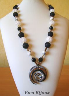 "Collier ""La Spirale"" avec pendentif en verre, perles en lave, en cristal de roche, en howlite et en verre."