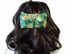 着物の変わり帯結び;文庫結びを型どったヘアアクセサリーです。結び方は、人気の文庫結びで舞妓さんの帯を思わせる可憐な印象となります。浴衣帯の結び方としてもよく用いられています。小桜の桜吹雪に、花明かりをぼかしで表現しています。桜は国花であり、一年中を通して使用して戴けます。また、緑はクリスマスカラーでもあり、クリスマスのプレゼントとしても喜ばれるのではないかと思います。バレッタは10cmの大きめのCLIPFRANCEを使用しており、まとめ髪も可能です。十分に気をつけておりますが、稀に接着剤のはみ出しがある場合が御座います。また、写真の撮り方により色彩のイメージが若干違う場合があります。ご了承の上、ご注文頂きますようお願い申し上げます。