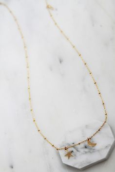 The Sibling Moon and Star Necklace is a delicate necklace comprised of a beaded gold chain with a petite moon and star charm. styling tip: Wear the Sibling Moon