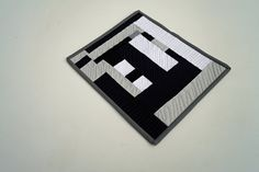 """Black, Grey and White Mini Quilt. This mini quilt will add some contemporary style wherever you put it - on a table as an oversize coaster, small place mat or little table covering, mug rug or snack mat. This monochromatic, black, grey and white quilt measures 11.25"""" X 9.5"""". Also a unique gift idea for the person who has everything."""