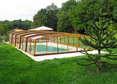 Wood-like imitation color used on pool enclosure VISION in the middle of large garden.