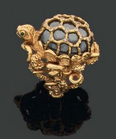 CARTIER RING turtle-shaped cabochon formed hematite in a golden cage mount. The body is formed of coiled serpents carved gold. Two emeralds for eyes. Signed and numbered.