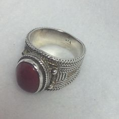 Sterling Cigar Band Style Ring w/ Red Agate Stone Ornate Sterling Silver wide cigar band style ring.  Beautiful Red Agate Cabochon is framed in center.  Cigar style is widest in top front area and tapers down in back to more narrow band.  Ring is a size 8, but is wide enough it would probably fit a size 7 or 7.5 better.  Pre owned, good condition.  Sterling could stand to be cleaned and polished again.  SEE MATCHING PENDANT AND EARRINGS. Unlisted Jewelry Rings