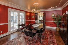 Dining room has decorative painting on walls and ceiling with French doors to mahogany deck .