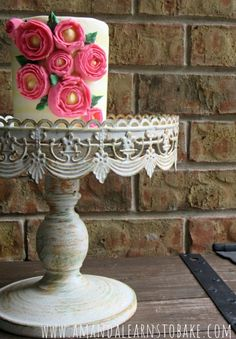 Cake Decorating Tutorial: Pinstripe buttercream with bright pink flowers. Find even more cake decorating tutorials at www.amandalearnstobake.com