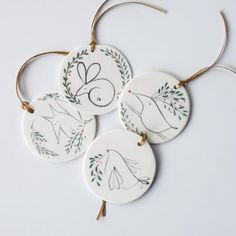 Scandi Style Christmas ornament set, decorated with handpainted images of woodland creature surrounded in a wreath of winter berry bush.They are made of a beautiful white porcelain clay, with line drawings of animals in black, green leaves and red berries. The set consists of :The Reindeer with beautiful, bushy, leafy antlers.The Hare, curled up in the cosy, green den.The Dove carrying a berry branch. The Fox dozing off in the undergrowth. The set ships in a gift box, ready for gift giving.Each Scandinavian Christmas Ornaments, Bird Christmas Ornaments, Clay Ornaments, Christmas Wreaths, Christmas Crafts, Christmas Time, Merry Christmas, Ceramic Pendant, Ceramic Art