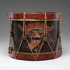 Background is brown with shield-breasted eagle holding ribbon inscribed U.S.S. Hartford, rims painted red. Drum heads are held with rope, leather tighteners, some replaced. Both heads present, with small area of loss to bottom head. Paint is still bright. 13 in. tall, 15.5 in. dia