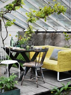modern high color sofa with vintage table and chairs make a lovely green house dining space