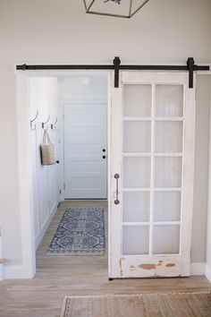 Antique door hung as barn door in laundry room I made sure to incorporate some of my favorite antique and vintage finds into every space of our home especially the addition of the barn doors - October 26 2019 at Wooden Garage Doors, Garage Door Design, Diy Barn Door, Diy Door, Barn Door With Window, Barn Door Garage, Wood Doors, Hanging Barn Doors, Glass Barn Doors