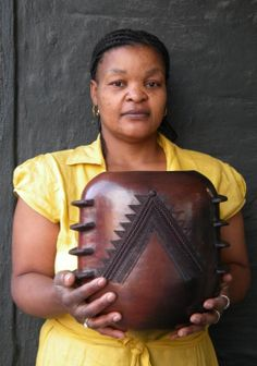 Africa | Jabu Nala holding one of her pots.  Jabu is the eldest daugher of Nesta Nala and has for some time now been pushing the boundaries as a transition away from 'just' the traditional Zulu beer pot.  It takes broad shoulders to make a pot like that.