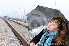 Smiling young woman with a sliver umbrella on the railroad