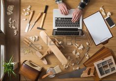 Man working on a DIY project with his laptop wood shavings and carpentry tools all around top view Stock Photo