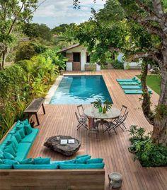 Espaçosa, a área externa tem sofá, mesa com cadeiras, espreguiçadeiras e piscina, além do gramado.