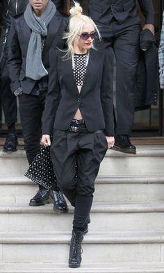 Bun, lipstick, black and white polka dot top, black blazer, black pants, black leather boots.