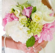 A bouquet of pink and white peonies, green hydrangeas, cream roses, and white calla lilies.