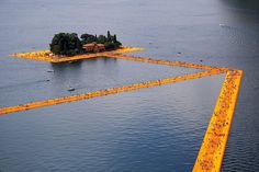 People walk on the monumental installation entitled 'The Floating Piers' created by artist Christo Vladimirov Javacheff on Iseo Lake, in northern Italy, on June 18, 2016. Some 200,000 floating cubes create a 3-kilometers runway connecting the village of Sulzano to the small island of Monte Isola on the Iseo Lake for a 16-day outdoor installation opening today. Courtesy of MARCO BERTORELLO/AFP/Getty Images.