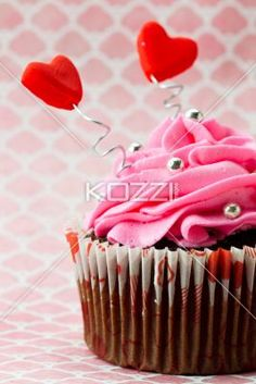 hearts sticking out of icing on a cupcake. - Hearts sticking out of icing on a cupcake on a pink surface.