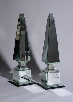 PAIR OF NEOCLASSICAL STYLE MIRRORED GLASS OBELISKS. With beveled edges, on ebonized wood bases - Dim: 23 3/4 x 7 in.