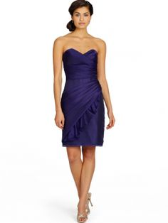 Organza cocktail length bridesmaid dress with a pleated front bodice and diagonally-pleated slim A-line skirt with ruffle accent.