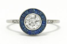 The Buellton Art Deco diamond engagement ring. This beautiful 1920s Jazz Age stunner is crafted of platinum and boasts a sparkling, fiery & bright old European diamond set low and snug in a secure bezel. You will love how the contrasting circle of calibre' cut, velvety-blue sapphires makes the diamond pop. #artdeco #engagementring #love #ido #platinum #diamond #sapphire #bluesapphire #haloring #halorings #targetring #targetrings #artdecoring #artdecorings #estatejewelry #secondhandjewelry… Estate Engagement Ring, Antique Engagement Rings, Diamond Engagement Rings, Art Deco Ring, Art Deco Diamond, Blue Sapphire Rings, Blue Rings, 1920s Jazz, Hand Jewelry