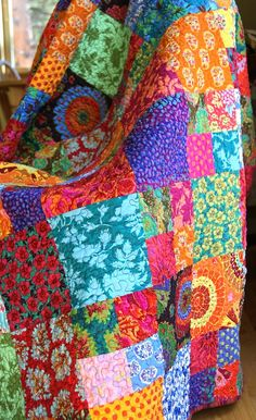 Heres a gorgeous handmade quilt that is actually two quilts in one. Its made with the brightest of the bright from Kaffe Fassett......fiery shades of orange, fuschia, violet, green, turquoise, yellow, and others are all tossed together in a beautiful scrappy pattern that shows them all off. The back is actually my favorite side of the quilt. It has a dusty rose print, scattered with flowers and stems in their little vases. In the center of the back, I have pieced random fabrics from the…