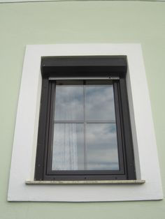 Very simple window with dark brown frame in green house.
