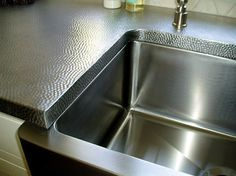 Brushed reverse hammered stainless steel countertops.