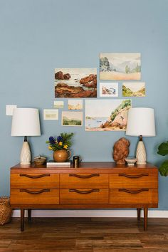 Gallery wall of vintage landscape paintings with mid-century modern dresser. Vintage eclectic home tour from Glitter Guide.