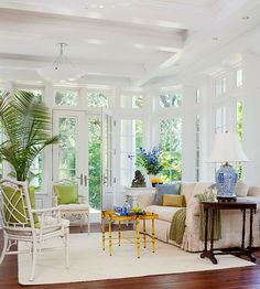Architecture takes center stage in this indoor-outdoor solarium living room. From the window mullion, to the transom windows and beamed ceiling, these extras supply visual variety in the small, window-filled room. Furniture choices complement the light and bright room, with rattan-style armchairs and tables as well as playful color selections and accents.