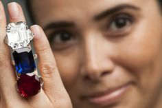 A Christie's employee poses with a 34.05 carat emerald-cut diamond ring, a 31.21 carat Burmese sapphire and diamond ring by Boucheron, and a 32.08 carat Burmese ruby and diamond ring by Chaumet. From Mrs. Lily Safra's Jewels for Hope auction, May 2012