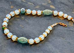 Yes! 1222155 | Bold opalite beads asymmetrically designed with blue, green, and clear lampworks beads, accented with vermeil brush bent disks. Closure is a vermeil hook clasp (can be lengthened for slight upcharge upon request.) Length 22 inches.  $275
