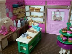 The left-hand side of the Li'l Woodzeez Bakery Shop. Notice that the gingerbread man can be removed from its mold. Each baguette, loaf of bread, bagel, etc are also removable from the display window. However, the items against the wall are glued to the shelves. And the oven door does open.