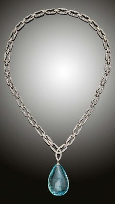 An Edwardian aquamarine and diamond pendant necklace, English, circa 1910. A large aquamarine briolette pendant suspended from a long pavé diamond set chain, mounted in platinum. The necklace can be split into various length necklaces and bracelets.