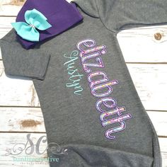This cute personalized gown is perfect for your little one or would make a great shower gift for mommies to be. It features the childs name appliqued down the front in a beautiful pink and aqua floral fabric outlined in purple on a charcoal gray gown and the childs middle name embroidered under.  To Order: 1) Childs First & Middle Name, if wanted  PLEASE NOTE: charcoal gowns and bodysuits are sized 3M and 6M; however, they measure the SAME as all of the other 0-3m or 3-6m gowns and bodysu...