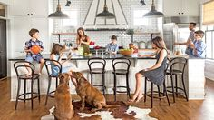 Crowd-Pleasing Kitchen - Life on the Lake - Southern Living - With five children and an endless stream of neighbors, Jen wanted to be able to mingle while she cooks, so Craft and Schnell set the kitchen along one wall of the home's open living and dining area. Its simple, rustic materials—butcherblock counters, pale subway tiles, a versatile 14- by 4-foot island wrapped in the same whitewashed pine as the living area's walls—help it blend into the main space rather than overtake it.