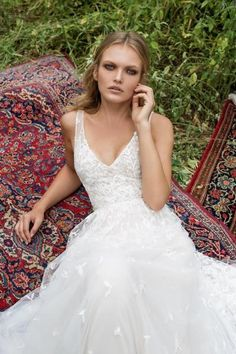 Aria is a beautiful embellished lace dress, with a full skirt made from layers and layers of tulle, which flows into a stunning detailed train. The dress features a deep v neckline and plunging v back.