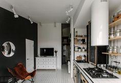 Il living della casa-studio di Mosca è a pianta aperta, con cucina disegnata da Sergei Semenov di studio Fineobjects. Gli arredi sono essenziali: tripolina in pelle effetto vissuto e mobile cassettiera di Ikea. Le piastrelle del pavimento sono in ceramica bianca
