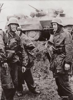German soldiers smoke captured American cigarettes in front of a U.S. Army armored car on December 17, the second day of Operation HERBSTNEB...