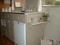 calming neutrals in a vintage camper. Make that shelf bigger and put on hinges for a drop down option.