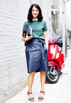 Black leather skirt is paired with a green top layered with a white shirt, red strap heels and a black clutch