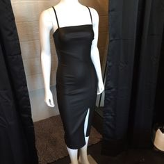 Midi Strap Fitted Dress with Front Slit in Black. Has a faux leather touch to the fabric.  Self: 100% Polyester Lining: 100% Polyester  (accessories shown with the garment are not included they are used for styling purposes)