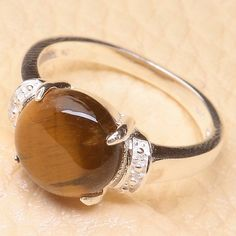 Solid .925 Sterling Silver ring set with round a round Tigers Eye stone. Ring…