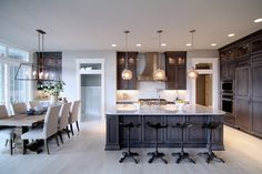 Incredible kitchen features stained wood cabinets adorned with brushed nickel pulls alongside white granite counters and a matching white granite backsplash which highlights a gas range and pot filler faucet under a stainless steel vent hood flanked by double stacked cabinets.