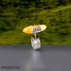 """Współczesny pierścionek zrobiony ręcznie ze srebra próby 925. Srebro jest młotkowane , oksydowane i polerowane . Ozdobą pierścionka jest bryłka bursztynu bałtyckiego 3,5cm na 1,4cm. Bursztyn został """"złapany """"  w srebrny gorset. Obrączka szerokości 8,5mm jest regulowana  i zaczyna sie od numeru 14,5. Na życzenie mogę zmniejszyć."""