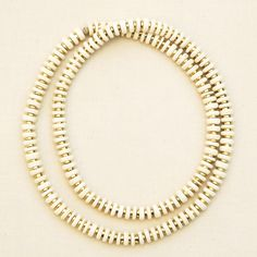 """Infinite single strand necklace. Brass heishi beads paired with bleached coconut palm wood. Small coated hemp knot at back. Slips overhead. One size. Approximately 17"""" long.  Great for layering. Shipped with logo-stamped drawstring bag."""