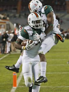 Miami wide receiver Stacy Coley jumps onto running back Gus Edwards as they celebrate a touchdown during the second half against Virginia Tech in an NCAA college football game in Blacksburg, Va., Thursday, Oct. 23, 2014. Miami won 30-6.